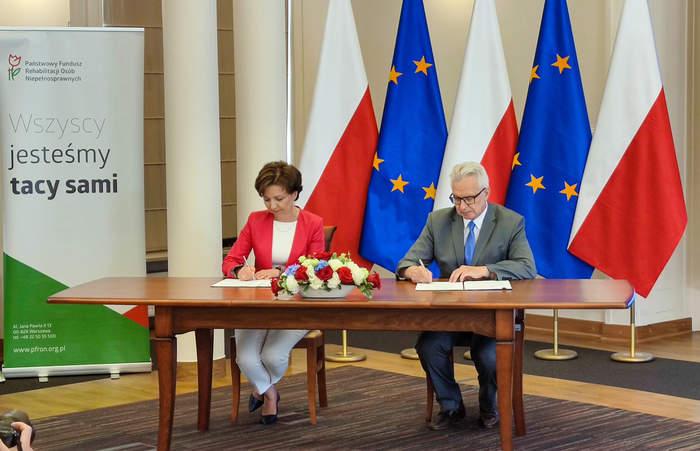 Pokaż zdjęcie: Kobieta i mężczyzna siedzą przy biurku i podpisują dokumenty. Na stole stoi bukiet kwiatów, w tle flagi polskie i unii europejskiej