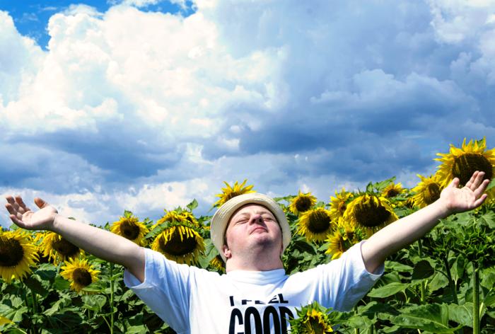 Pokaż zdjęcie: mężczyzna z Zespołem Downa na tla niebieskiego nieba i słoneczników